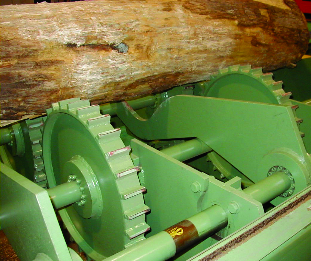 Heavy Duty B112 Keyless Bushings connect barking wheels and kicker arms on a log debarker